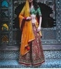 red zardozi embroidered bridal lehanga and green brocade blouse with a yellow dupatta